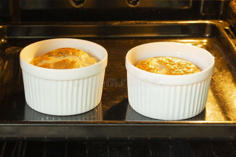 Omelette d'oeufs en bidons blancs cuits au four dans le four, petit déjeuner pour deux parties, faisant la nourriture photos libres de droits