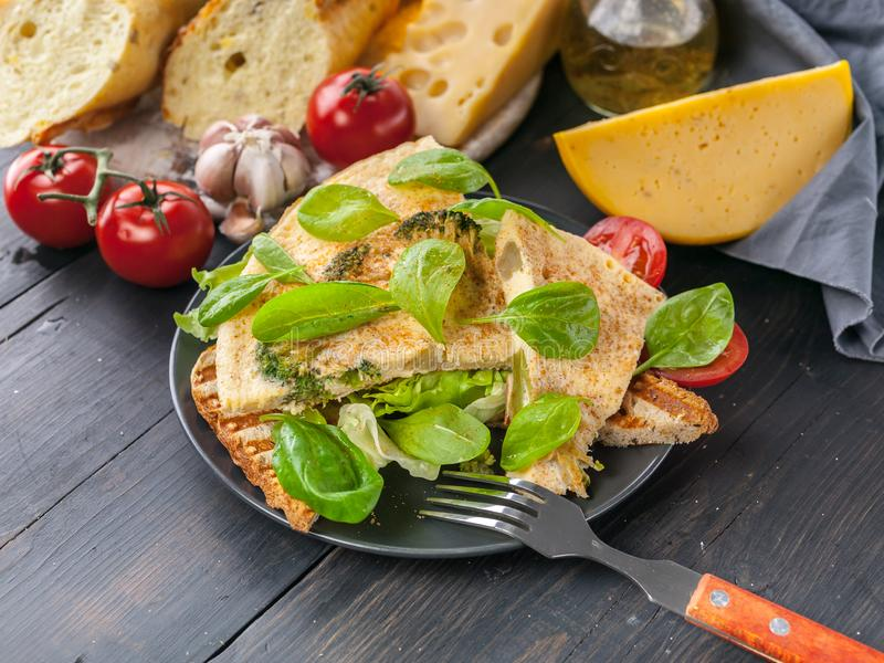 Omelette del primo piano con le foglie delle verdure, del formaggio e degli spinaci su pane tostato con l'insalata del ghiaccio P immagini stock