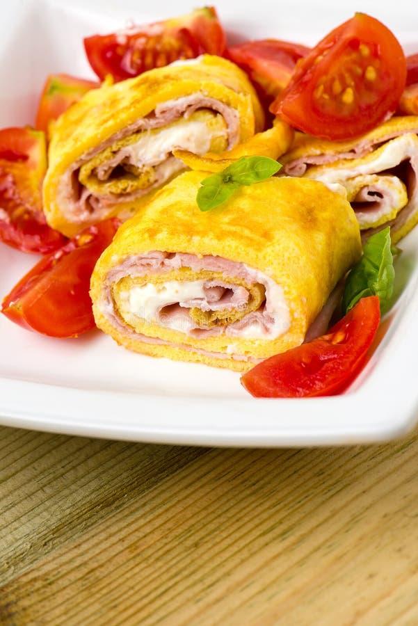 Omelette deliziosa dei rotoli con la crema del pomodoro, del prosciutto e del formaggio fotografie stock libere da diritti