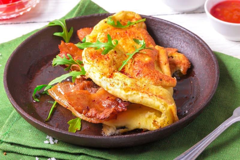 Omelette deliziosa del bacon con la rucola ed i pomodori marinati variopinti Fine in su fotografie stock