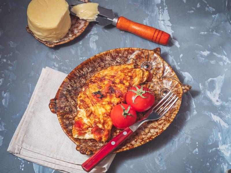 Omelette du MZ de petit déjeuner avec les légumes et le fromage Plats décoratifs, deux tomates rouges entières avec des feuilles  photographie stock