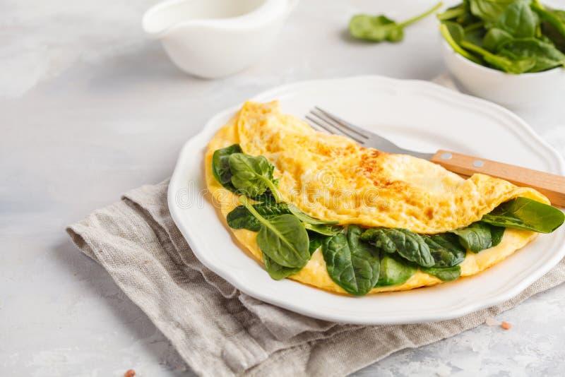 Omelette farcita con spinaci e formaggio per una prima colazione Breakf fotografia stock
