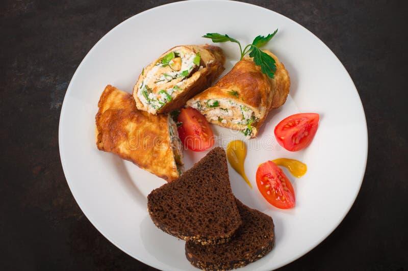 Omelette française faite maison avec le fromage blanc, les herbes et les tomates Vieux fond rustique noir Vue supérieure photographie stock libre de droits