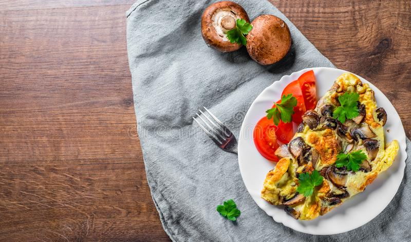 Omelette with mushrooms in white plate on wooden table royalty free stock images