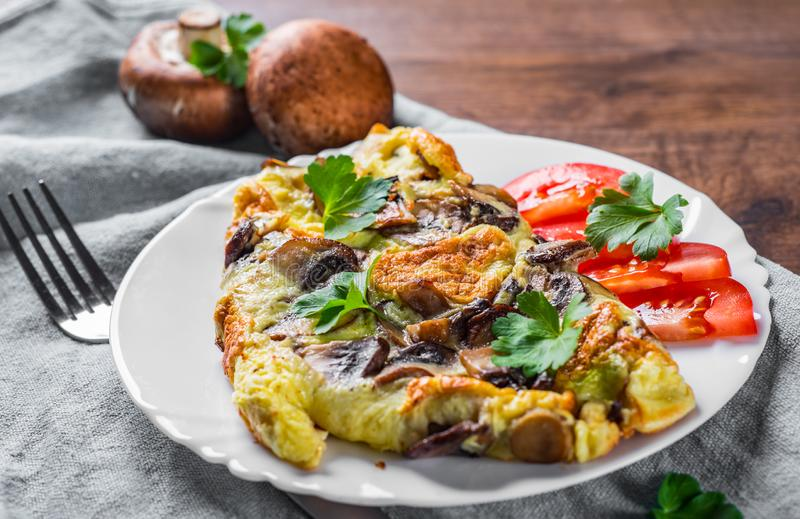 Omelette with mushrooms in white plate on wooden table royalty free stock image