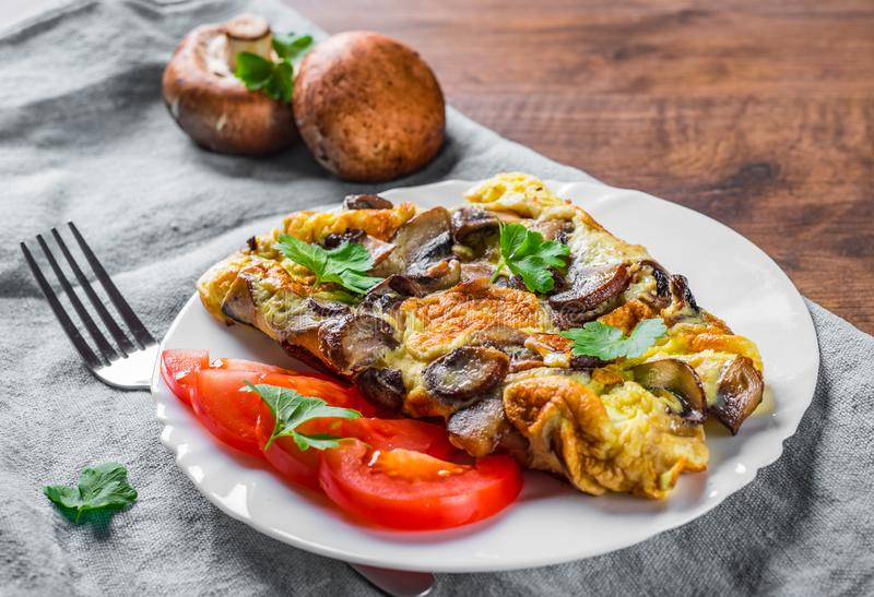 Omelette with mushrooms in white plate on wooden table stock photography