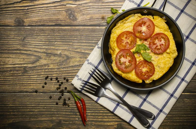 Omelette in a pan that is placed on a wooden background royalty free stock image
