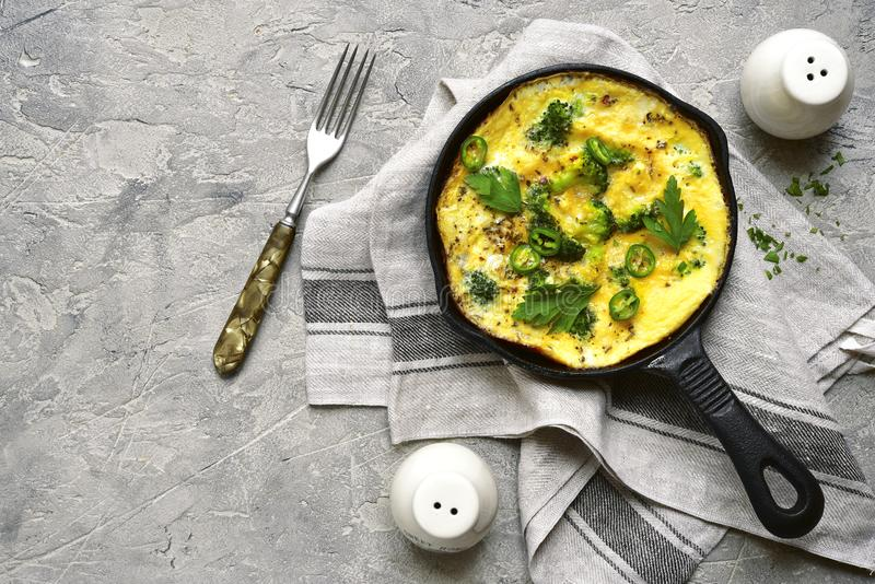 Omelette rustique avec le brocoli et le fromage dans une casserole noire de fer dessus image libre de droits