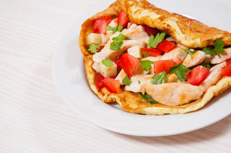 Omelette with slices of chicken breast, cheese and vegetables royalty free stock images