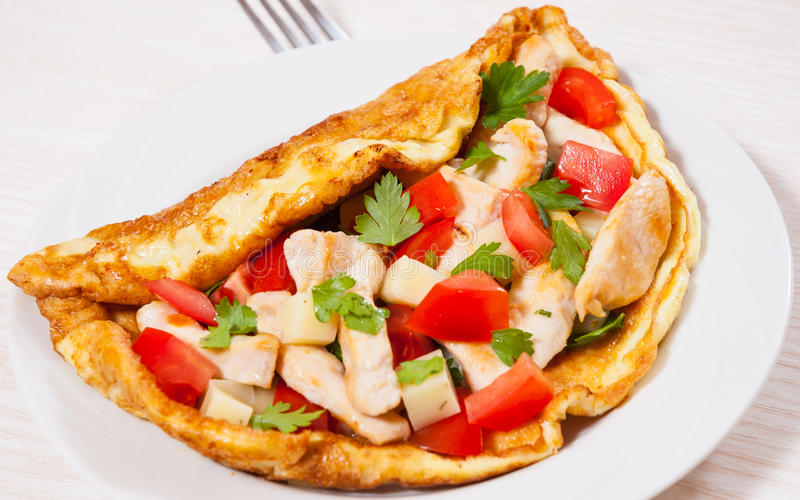 Omelette with slices of chicken breast, cheese and vegetables stock images
