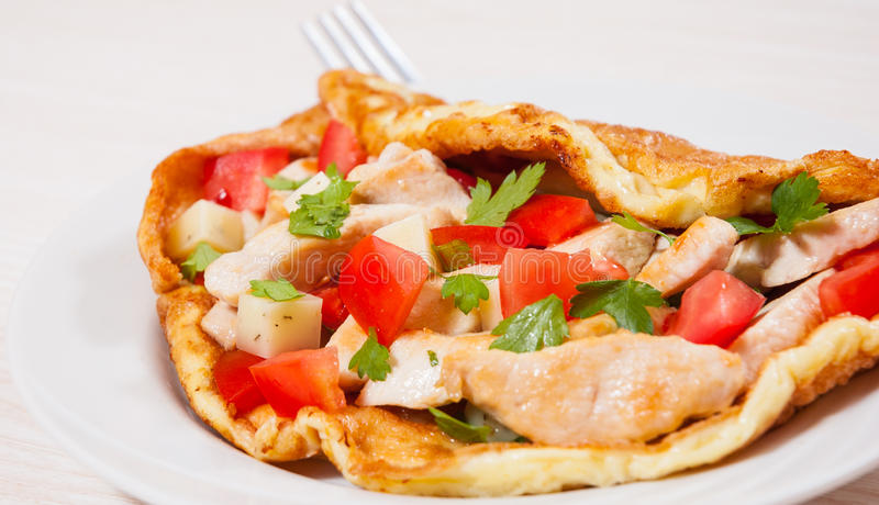 Omelette with slices of chicken breast, cheese and vegetables stock image