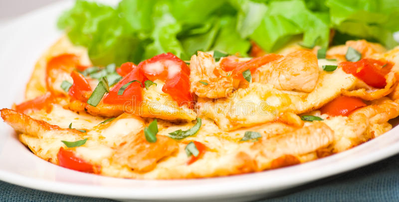 Omelette with slices of chicken breast and vegetables stock images