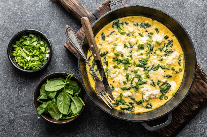 Omelette with spinach and cheese in a pan top view stock photos