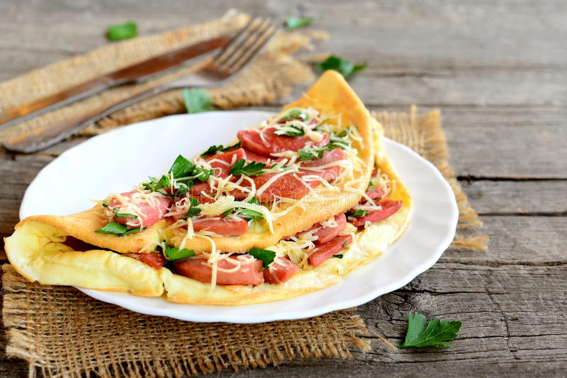Omelette stuffed with fried sausages, grated cheese and parsley on a plate, fork, knife and an old wooden table. Eggs breakfast. Breakfast omelette. Eggs stock photography