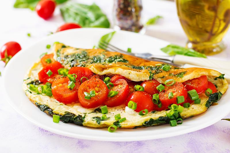 Omelette with tomatoes, spinach and green onion on white plate. stock images