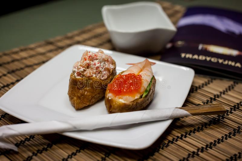 Omelettsushi mit Reis und Salat mit Lachsen, Garnelen und Kaviar lizenzfreie stockbilder