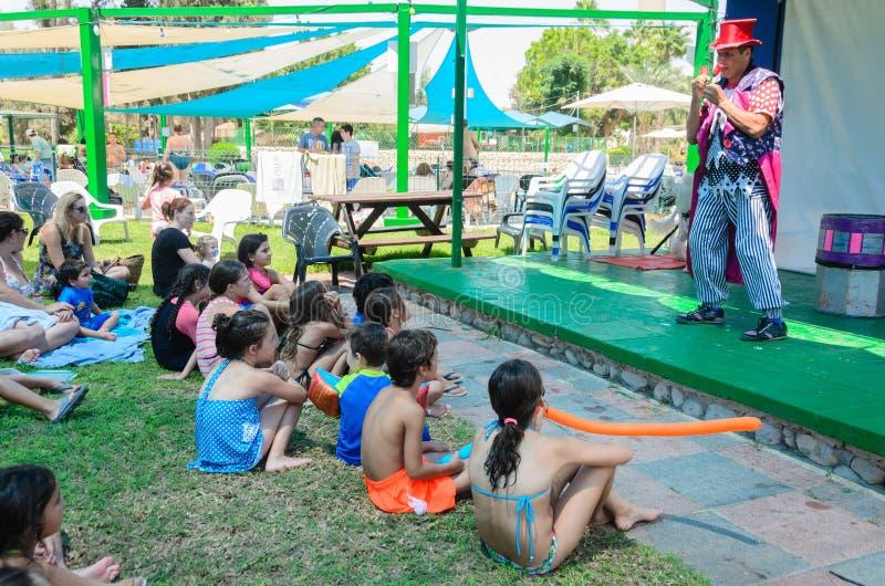 Omer (пиво-Sheva), ИЗРАИЛЬ - клоун говорит к детям на этапе около бассейна, 25-ое июля 2015 лета в Израиле стоковое фото