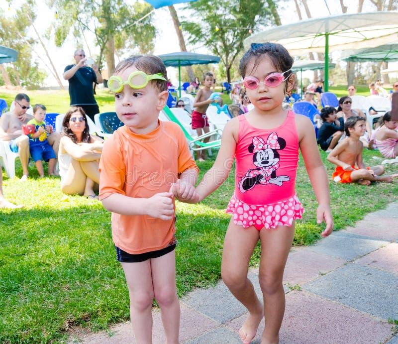 Omer (пиво-Sheva), ИЗРАИЛЬ - мальчик и девушка в изумлённых взглядах заплывания с другими детьми на траве бассейном, 25-ое июля 2 стоковые фотографии rf