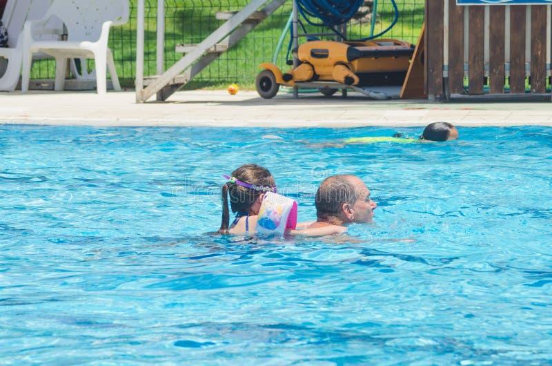 Omer (пиво-Sheva), ИЗРАИЛЬ - отец и дочь плавают в бассейне 25-ое июля 2015 стоковые изображения