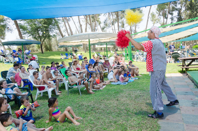 Omer (Beer-Sheva), ISRAEL -Clown plays with children sitting on the grass, July 25, 2015 stock photos
