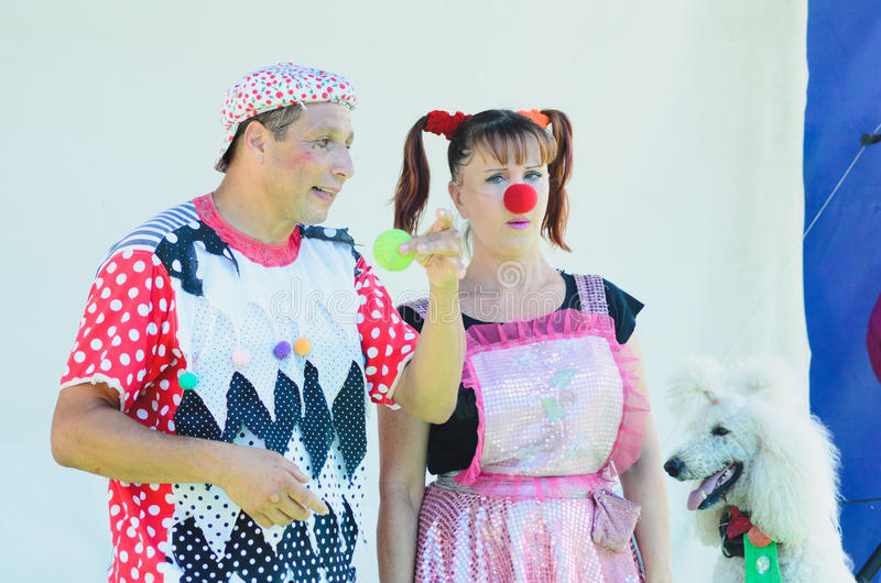 Omer (Beer-Sheva), ISRAEL - Clowns with a tennis ball and a white poodle, July 25, 2015 in Israel, July 25, 2015 stock photos