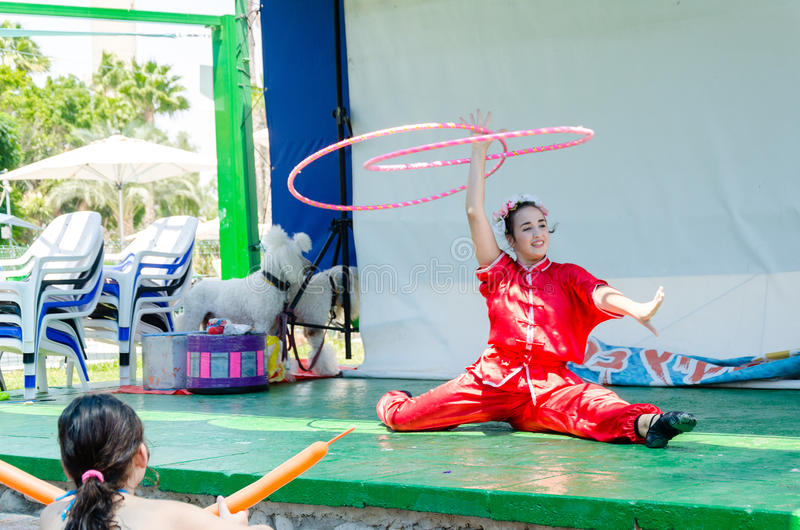 Omer (Beer-Sheva), ISRAEL -The girl in a scarlet kimono sits in the splits and rotates hoops on an outdoor stage, July 25, 2015. Beer-Sheva, ISRAEL -The girl in stock photography