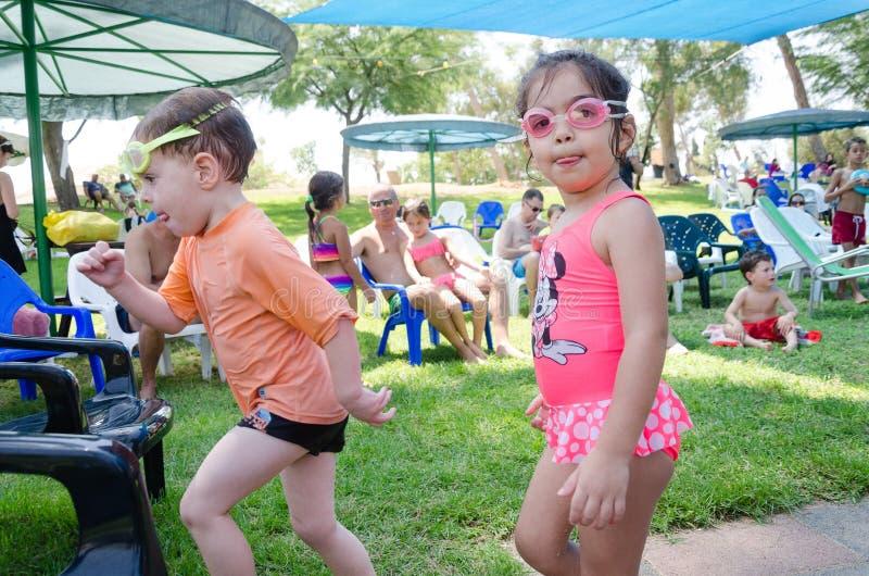 Omer (bière-Sheva), l'ISRAËL garçon et la fille dans des lunettes de natation avec d'autres enfants près de la piscine, le 25 jui photos libres de droits