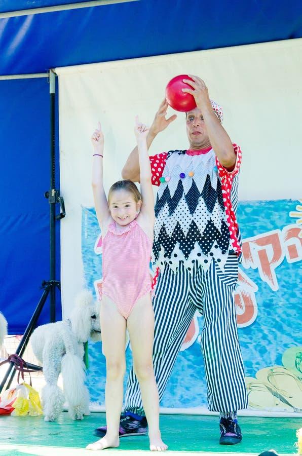 Omer (birra-Sheva), ISRAELE - Clown con una palla e una ragazza in un costume da bagno rosa, il 25 luglio 2015 immagini stock libere da diritti