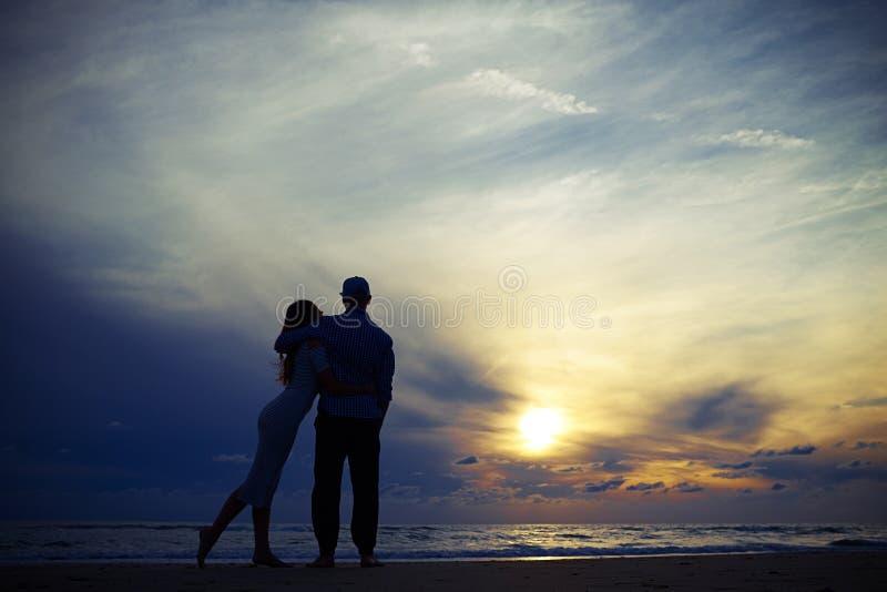 Omfamna för värme av lyckliga romantiska par som är förälskade på stranden a arkivbild