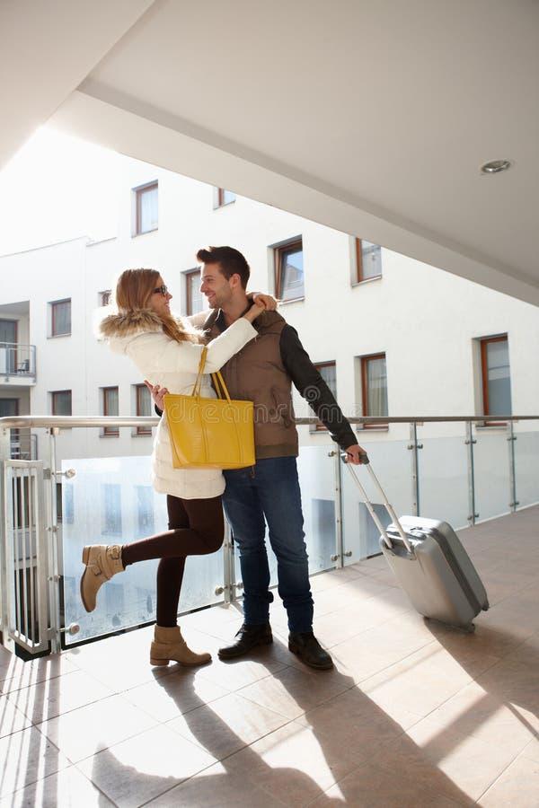 Omfamna par med bagage royaltyfri bild