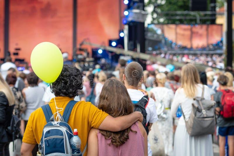 Omfamna ungdomarsom står, i folkmassan och att hålla ögonen på en frilufts- konsert tillbaka sikt royaltyfria bilder