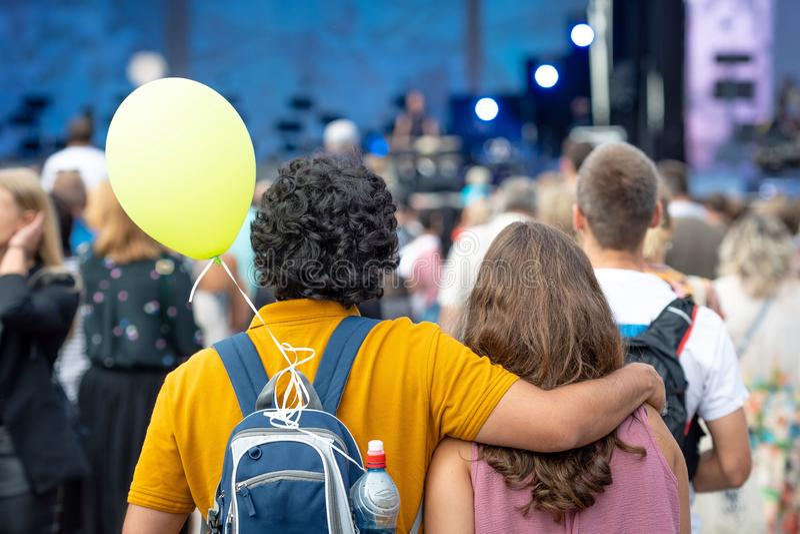 Omfamna ungdomarsom står, i folkmassan och att hålla ögonen på en frilufts- konsert tillbaka sikt royaltyfri fotografi