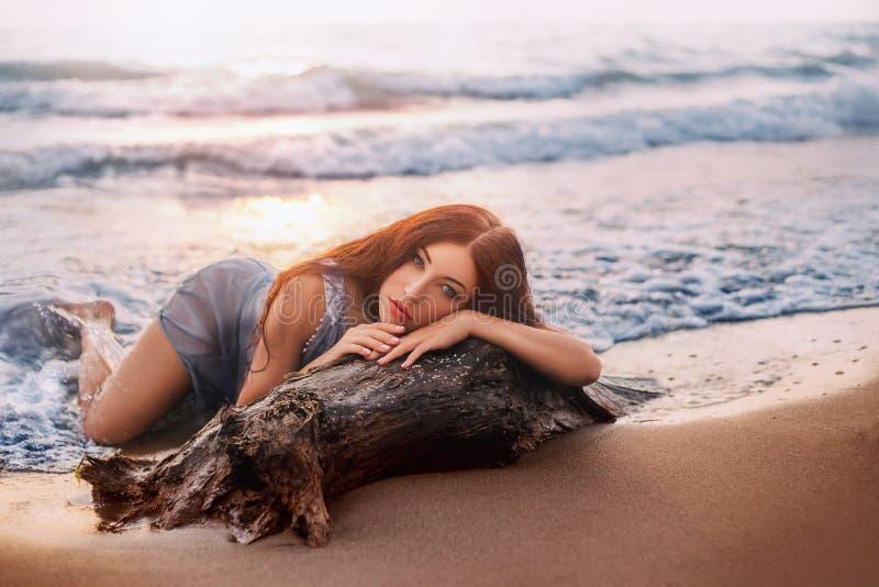 Omformningen av en sjöjungfru En kvinna i en våt klänning ligger på stranden royaltyfria bilder