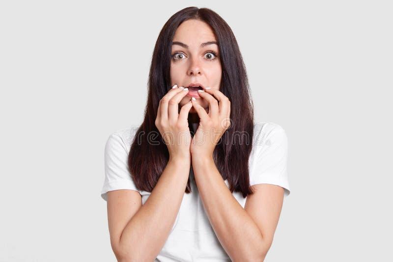 Omg,它可怕!Shocked让有害怕的表情的妇女担心,在嘴附近保留手,听见可怕的新闻,佩带白色c 图库摄影