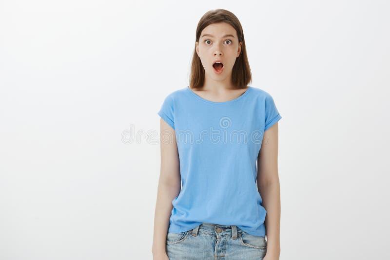 Omg,没有方式它是真正的 Shocked打动了蓝色T恤杉,滴下的下颌和凝视的滑稽的女孩在与兴趣的照相机 库存图片
