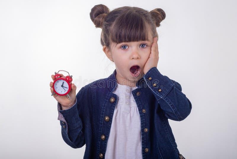 Omg, budzi się! Zdziwiona dziewczyna w sukni z czerwień zegarem na białym tle Szokujący dzieciaka mienia budzik obraz royalty free