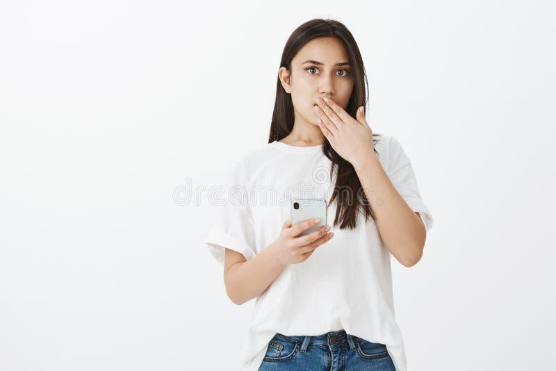 Omg, che ha inviato il messaggio Shocked ha stupito l'amica attraente con l'attrezzatura casuale, tenendo lo smartphone, mandibol immagine stock