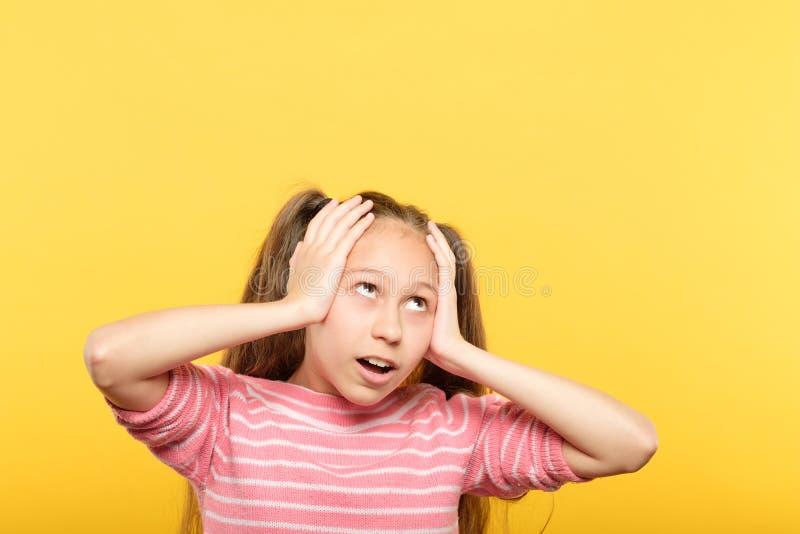 Omg chocou a menina que olha acima de agarramento as mãos principais imagem de stock royalty free