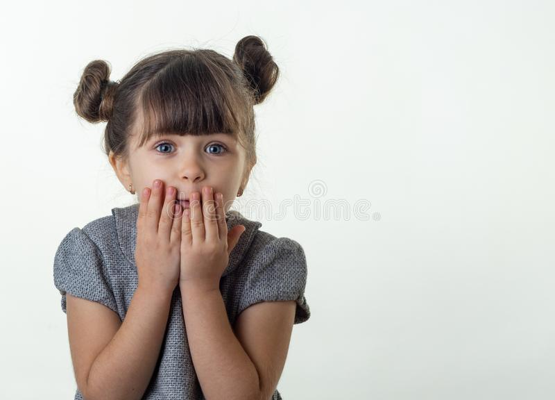 OMG! Happy surprised child 4 or 5 years old isolated on white. Oh no! Terrified shocked child with bugged eyes covers mouth with h royalty free stock photos