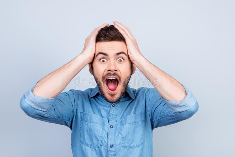 Omg! Keine Weise! Sehr entsetzter junger Mann hält seinen Kopf mit Stückchen lizenzfreie stockbilder
