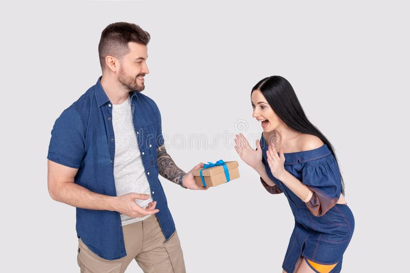 Omg. Profile side view photo of surprised pretty lady getting giftbox felicitations from bearded handsome sweetheart waving hands royalty free stock photography