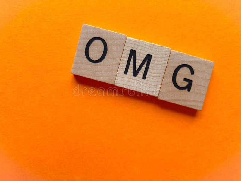 OMG in wooden letters isolated on orange royalty free stock photo