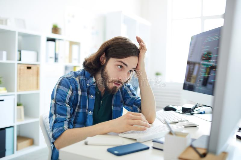 Omg. Young confused it-manager looking at one of computer monitors with tense expression royalty free stock photos