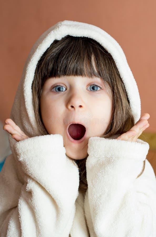 OMG! Zdziwiony dzieciak jest ubranym bathrobe po skąpania lub prysznic Kąpanie i domycie dzieci obraz royalty free