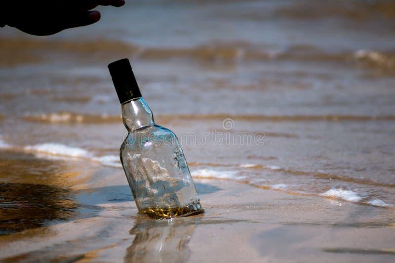 Omgedraaide die glasfles in het zand met golven, branding en zand op de achtergrond bij Diu-strand Gujarat India wordt begraven stock afbeelding