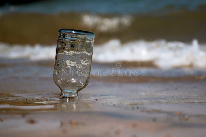 Omgedraaide die glasfles in het zand met golven, branding en zand op de achtergrond bij Diu-strand Gujarat India wordt begraven stock foto