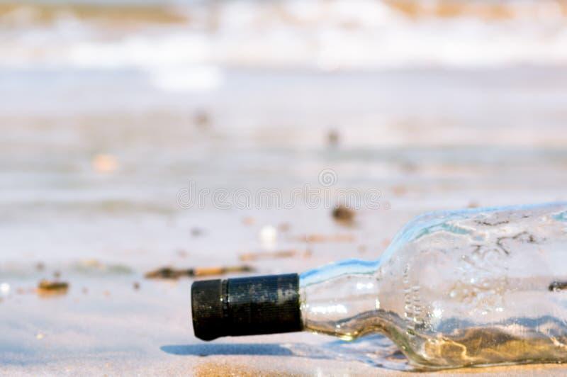 Omgedraaide die glasfles in het zand met golven, branding en zand op de achtergrond bij Diu-strand Gujarat India wordt begraven royalty-vrije stock foto's