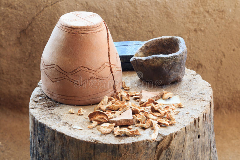 Omgekeerde ceramische pot die zich op een boomstomp bevinden met droge paddestoelen stock foto's