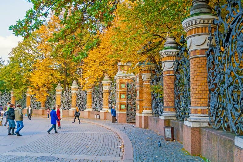 Omheining van Michael Garden in St. Petersburg, Rusland en toeristen die in de herfstdag lopen stock afbeeldingen