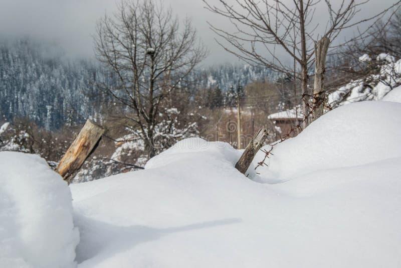 Omheiningsdetails in sneeuw in de winterlandschap worden behandeld - de bevroren het weerhaakdraad en hout bij sneeuw behandelden royalty-vrije stock foto